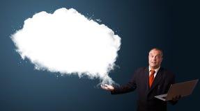 Biznesmen trzyma laptop i przedstawia abstrakt chmury kopię Obraz Royalty Free