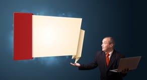 Biznesmen trzyma laptop i przedstawia nowożytną origami kopię Fotografia Stock