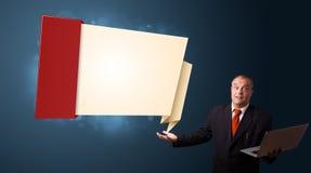 Biznesmen trzyma laptop i przedstawia nowożytną origami kopię Obraz Royalty Free