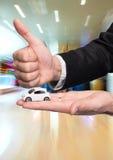 Biznesmen trzyma małego samochodu modela i pokazuje ok w czarnym kostiumu Fotografia Royalty Free