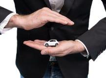 Biznesmen trzyma małego samochodu modela w czarnym kostiumu Zdjęcia Stock