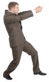 Biznesmen trzyma niewidzialnego pistolet Obrazy Stock