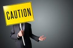 Biznesmen trzyma ostrożność znaka obrazy stock