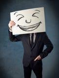 Biznesmen trzyma papier z smiley twarzą przed jego hea zdjęcie stock