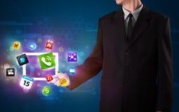 Biznesmen trzyma pastylkę z nowożytnymi kolorowymi apps i ikonami royalty ilustracja