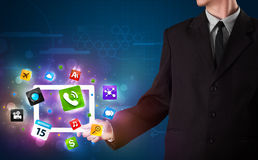 Biznesmen trzyma pastylkę z nowożytnymi kolorowymi apps i ikonami Obrazy Stock