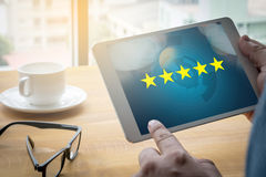 Biznesmen trzyma pięć gwiazdową ocenę, przegląd, przyrostowa ocena lub zdjęcia royalty free