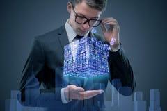 Biznesmen trzyma pieniężnego sześcian w biznesowym pojęciu Fotografia Stock