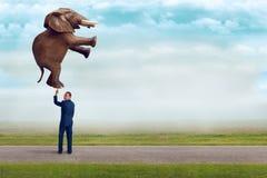 Biznesmen trzyma słonia z jeden palcem fotografia stock