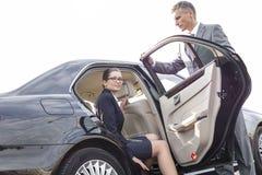 Biznesmen trzyma samochodowego drzwi dla kolegi przeciw niebu zdjęcia royalty free
