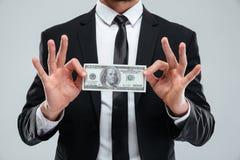 Biznesmen trzyma sto dolarów banknotów w kostiumu i krawacie Obraz Stock