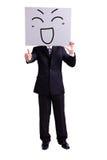 Biznesmen trzyma szczęśliwego wyrażeniowego billboard zdjęcia stock