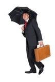 Biznesmen trzyma teczkę z parasolem Zdjęcie Royalty Free