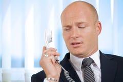 Biznesmen trzyma telefonicznego odbiorcę przy biurem Obrazy Royalty Free