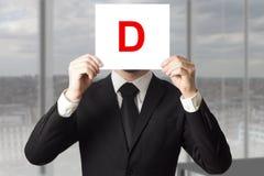 Biznesmen trzyma up szyldowy z listowym d w kostiumu Fotografia Royalty Free