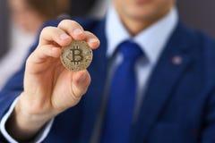 Biznesmen trzyma złotego bitcoin i ono uśmiecha się Wirtualny anonimowy pieniądze pojęcie, sukces w cyfrowym finanse obraz stock