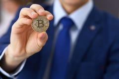 Biznesmen trzyma złotego bitcoin i ono uśmiecha się Wirtualny anonimowy pieniądze pojęcie, sukces w cyfrowym finanse fotografia royalty free