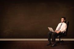 Biznesmen trzyma zaawansowany technicznie laptop na tle z copyspac Zdjęcia Stock