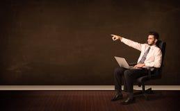 Biznesmen trzyma zaawansowany technicznie laptop na tle z copyspac Obraz Royalty Free