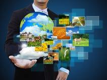 Biznesmen trzyma zieloną ziemię w rękach Obrazy Royalty Free