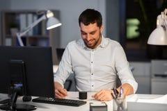 Biznesmen używa mądrze mówcy przy nocy biurem zdjęcia royalty free