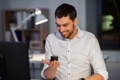 Biznesmen używa mądrze mówcy przy nocy biurem fotografia royalty free