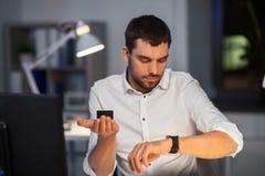 Biznesmen używa mądrze mówcy przy nocy biurem obrazy stock