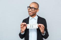 biznesmen uśmiecha się dolarowego banknot i trzyma Obrazy Stock