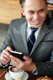 Biznesmen uśmiecha się telefon komórkowego i trzyma Zdjęcia Stock