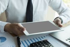 Biznesmen używa cyfrową pastylkę w biurze młody męski początek u Zdjęcie Stock