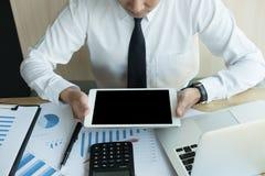 Biznesmen używa cyfrową pastylkę w biurze młody męski początek u Obraz Royalty Free