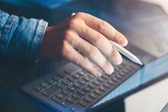 Biznesmen używa elektroniczną pastylka doku stację przy biurem Zbliżenie męska ręka wskazuje na przyrządu ekranie Obraz Royalty Free