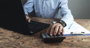 Biznesmen używa kalkulatora i działania na laptopie Biznesowy przeciw fotografia stock
