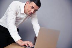 Biznesmen używa laptop i patrzejący kamerę Zdjęcia Royalty Free