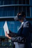 Biznesmen używa laptop i rzeczywistość wirtualna szkła Zdjęcia Stock