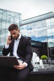 Biznesmen używa laptop podczas gdy opowiadający na telefonie Obraz Royalty Free