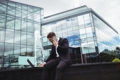 Biznesmen używa laptop podczas gdy opowiadający na telefonie Zdjęcie Royalty Free