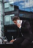 Biznesmen używa laptop podczas gdy opowiadający na telefonie Zdjęcie Stock