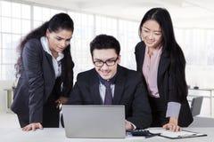 Biznesmen używa laptop z dwa podwładnymi Zdjęcie Royalty Free