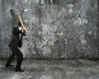 Biznesmen używa młota łupania ścianę łamającą na betonie fotografia stock