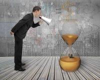 Biznesmen używa megafon wrzeszczy przy mężczyzna zalewał w hourglass Obraz Stock