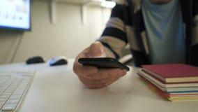 Biznesmen używa nowożytnego smartphone przy jego biurowym miejscem pracy podczas gdy pracujący zdjęcie wideo