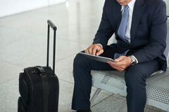 Biznesmen używa pastylka komputer w lotnisku obraz stock