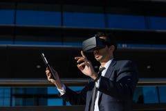 Biznesmen używa pastylki rzeczywistości wirtualnej i komputeru szkła Zdjęcie Royalty Free