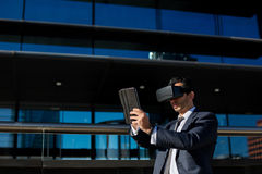 Biznesmen używa pastylki rzeczywistości wirtualnej i komputeru szkła Zdjęcie Stock