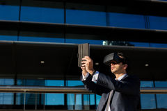 Biznesmen używa pastylki rzeczywistości wirtualnej i komputeru szkła Fotografia Stock