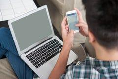 Biznesmen używa smartphone i laptop na kanapie zdjęcie stock