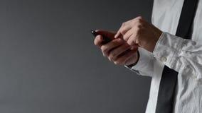 Biznesmen używa smartphone. Ręki scrolling ekran i pisać na maszynie. zbiory