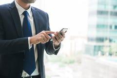 Biznesmen używa telefon komórkowego app texting na zewnątrz biura w miastowym mieście z drapaczy chmur budynkami w tle fotografia stock