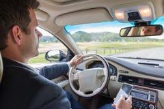 Biznesmen używa telefon komórkowego i texting podczas gdy jadący no płacić uwagi droga Fotografia Stock